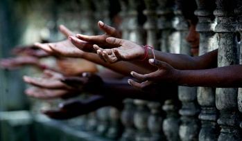 Children hands reaching through a gate