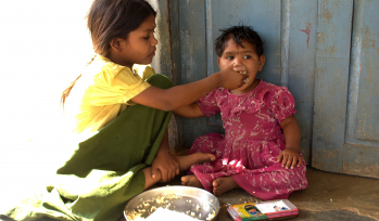 Older child feeding a younger child