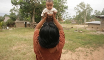 Adult lifting up a baby