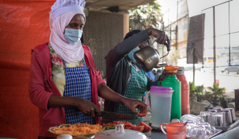 Alt =  young Ethiopian women selling street food during COVID-19 pandemic