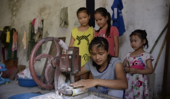 Children using a piece of sewing equipment