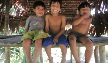 """Alt=""""Photo of three young boys sitting on a wooden bench, smiling into the camera."""""""
