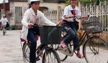 Two girls ride their bikes through town