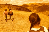 Three girls walking across a hillside