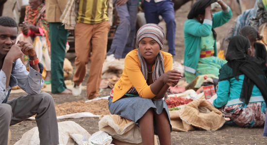 Young person sat in a market