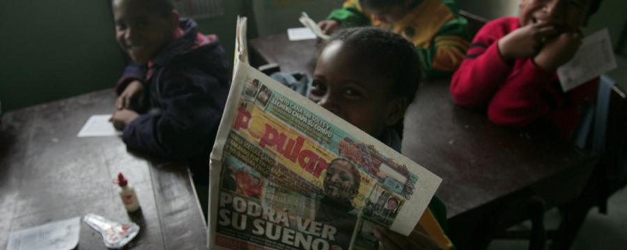 Children reading a newspaper