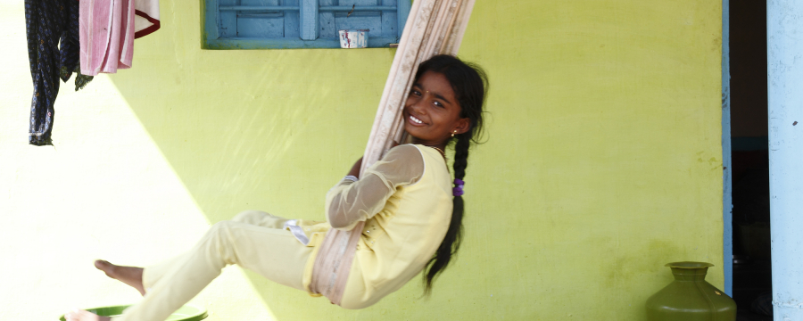 Child on a swing outside their house