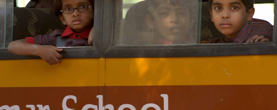 Children looking out the window of a school bus