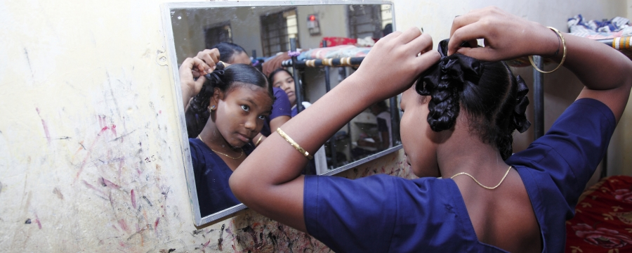 Child sorting out their hair in the mirror