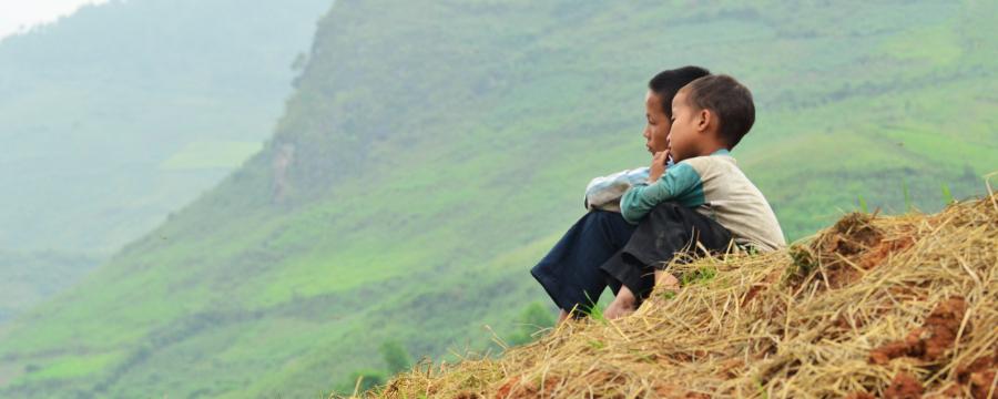 Two boys sat on a hillside