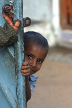 Young boy peering round a gate