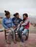 Three women sat on a bench