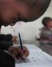 Young boy writing down school work