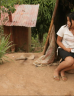 Young Peruvian girl sitting outside her house in the jungle