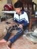 Boy weaving a straw hat