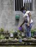Masked girl watering her garden