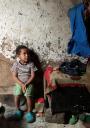 Child say alongside a wall